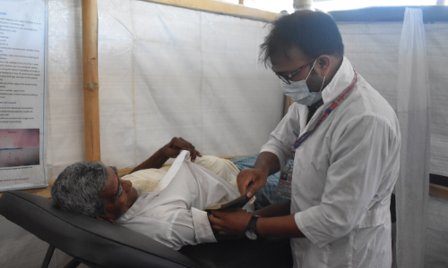 A healthcare worker treats an older person in Cox's Bazar, Bangladesh