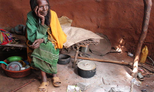 An older woman in Ethiopia sits, head in hands, in her home