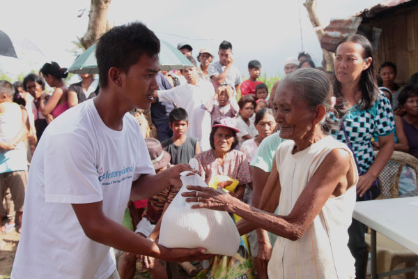 An Age International worker gives food to an older woman after the 2013 typhoon in Philippines