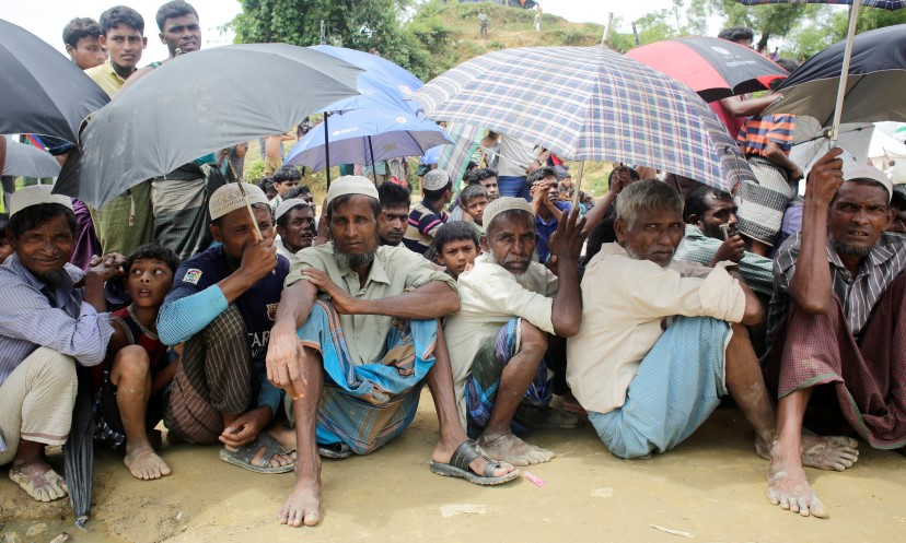 Older Rohingya refugees shelter from the rain in a refugee camp in Bangladesh.
