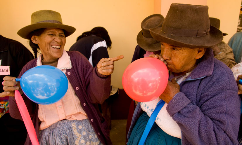 Two older women blow up balloons for a celebration in Peru