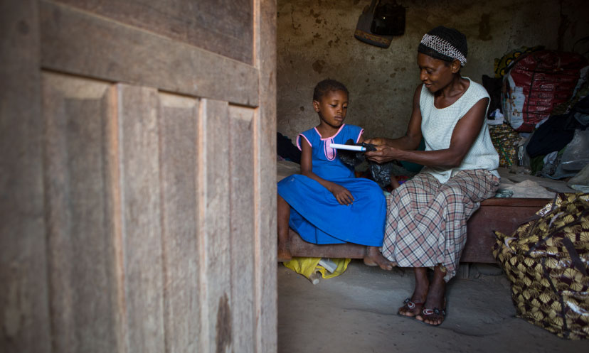 A grandmother gives her granddaughter her school book in Sierra Leone